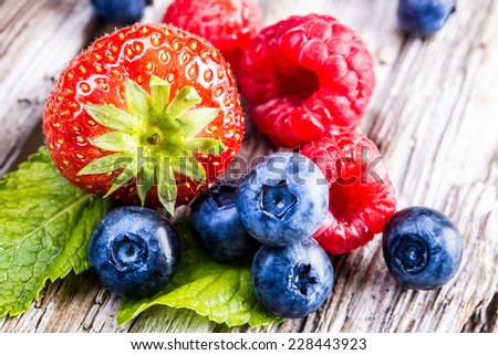 Berry fruits on wooden background or table. Blueberries, raspberries, strawberries, Forest fruits. Gardening ,agriculture,harvest and forest concept.  - stock photo