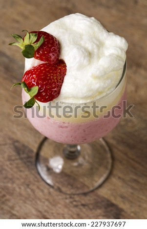 Berry smoothie or milkshake in a tall glass made from a blend of fresh strawberries and raspberries with frozen yoghurt or ice cream for a refreshing summer beverage - stock photo
