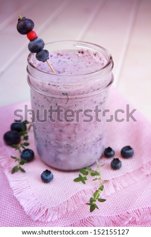 Berry smoothie with blueberry and herbs on a tablecloth - stock photo