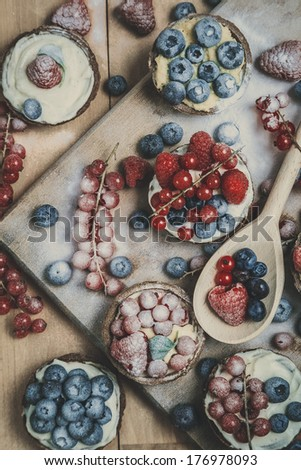 Berry tartlets in powdered sugar on wooden table, look from above - stock photo