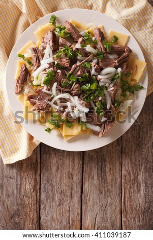Beshbarmak dish: noodles with lamb and onion close-up on a plate on the table. Vertical top view - stock photo