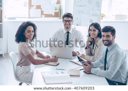 Best business team ever! Group of cheerful coworkers looking at camera with smile while sitting at the office table  - stock photo