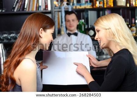Best choice of drinks. Two beautiful women discussing bar menu copyspace with barman standing behind the counter - stock photo