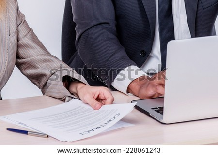 Best day to work together. Two smiling businessman looking at each other while businessmen sitting at a table working on a laptop showing a thumbs up on a gray background. - stock photo