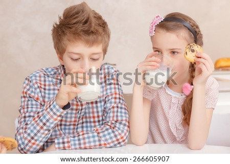 Best dessert. Small children having a glass of milk with home-made pastry  - stock photo