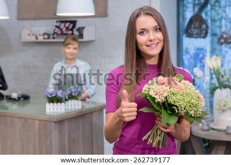 Best flowers for special occasion. Attractive young woman holding a bouquet raises her thumb up showing satisfaction with the purchase - stock photo