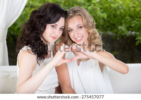 Best friends - beautiful young women showing heart sign with their hands, sitting in summer cafe.  - stock photo