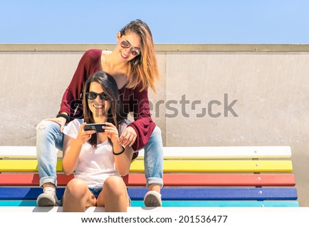 Best friends enjoying time together outdoors with smartphone - Concept of new technology with two girlfriends having fun on a multicolored bench - stock photo