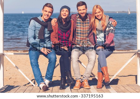 Best friends ever. Full length of four young happy people bonding to each other and smiling while sitting on the beach - stock photo