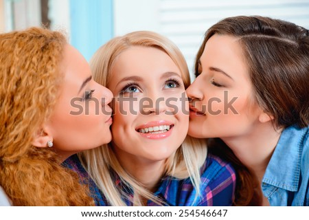 Best friends for life. Three young beautiful female friends sitting in cafe and kissing each other - stock photo