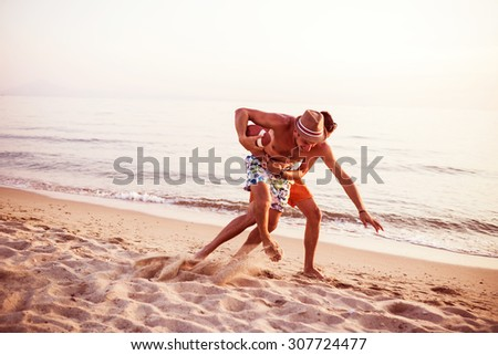 Best Friends playing Football On Beach. Depth of field, selective focus - stock photo