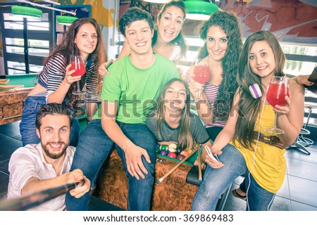 Best friends taking selfie at billiard pool table with back lighting - Happy friendship concept with young people having fun  - Vintage filtered look with soft focus on face due to sunshine halo flare - stock photo