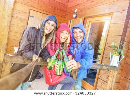 Best friends taking tilted selfie at camping bungalow with sunshine after the rain - Youth and freedom concept outdoors in autumn vacations - Young people having fun and cheering with bottled beer - stock photo