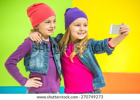 Best friends. Two cute little girls doing selfie on colorful background. - stock photo