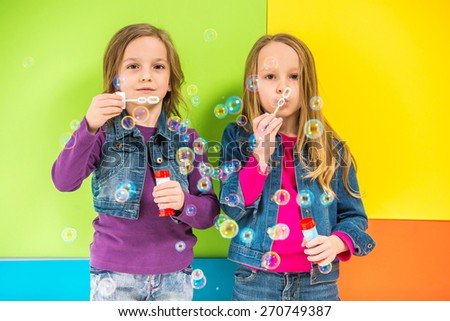 Best friends. Two cute little girls having fun with bubbles  on colorful background. - stock photo