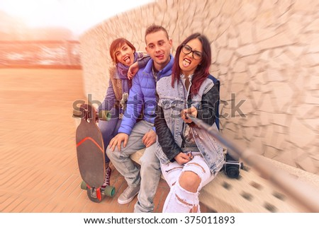 Best friends using selfie stick making funny faces - Concept of friendship and travel with young people and new technology trends - Brown filter with artificial sunlight and radial zoom defocusing - stock photo