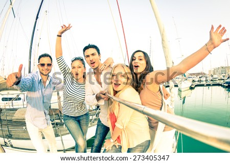 Best friends using selfie stick taking pic on exclusive luxury sailing boat - Concept of friendship and travel with young people and new technology  trends - Bright nostalgic desaturated color tones - stock photo
