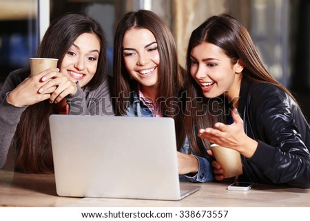 Best friends with laptop together sitting at cafes terrace - stock photo