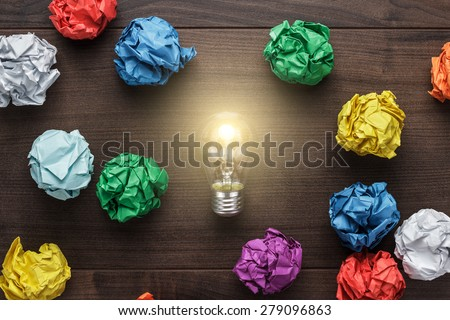 best idea concept with crumpled colorful paper and light bulb on wooden table - stock photo