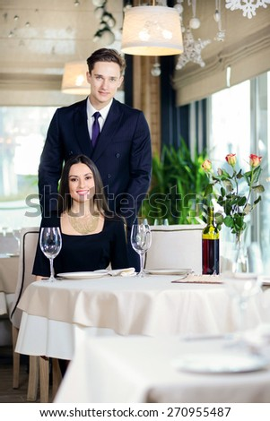 Best love romantic dinner in a restaurant. Young loving couple visits a restaurant. Woman standing near a man while the man sat down at the table and a woman looking directly into the camera - stock photo