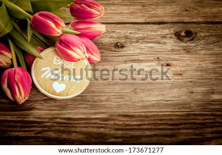Best Mama greeting card on grunge rustic wood with a bunch of fresh red tulips in the corner and copyspace for your text on Mothers Day or for a Baby Shower - stock photo