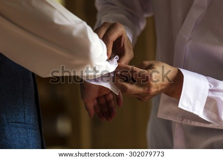 Best man helping groom with cufflinks - stock photo
