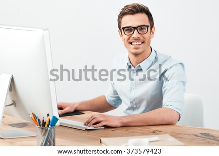 Best manager. Cheerful young handsome man in glasses working on computer and looking at camera with smile while sitting at his working place - stock photo