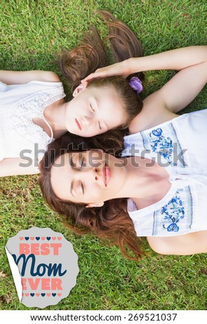 best mom ever against mother and daughter lying on grass - stock photo