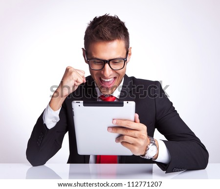best news received by a business man by email on his brand new touchscreen pad - stock photo