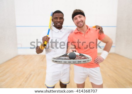 Best partners in squash on court. Happy men holding rackets with ball and looking at camera. Sporty men playing tennis. - stock photo