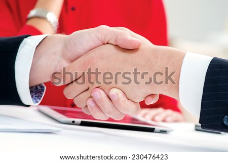 Best partners. Three successful and confident businesspeople shake hands. Businesspeople in formal attire sitting in an office at a desk close-up view of hands - stock photo