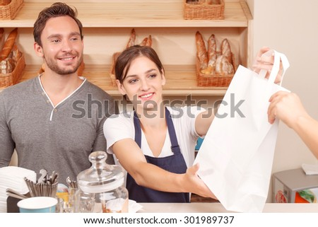 Best service. Portrait of youthful beautiful female cafeteria worker standing near her colleague and serving client - stock photo