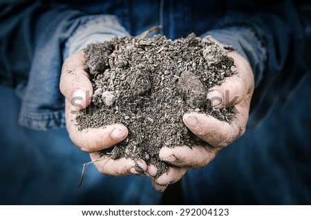 best soil in farmer hands macro image with selective focus - stock photo