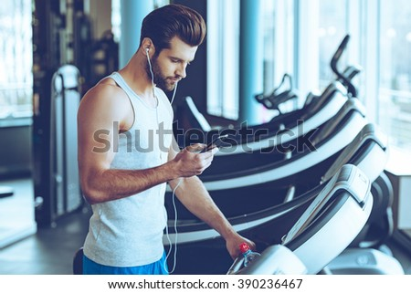 Best song for his training. Side view of young handsome man in sportswear using his smart phone while standing on treadmill at gym - stock photo