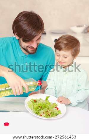 Best time together. Close-up of a young father and his son making salad dressing together - stock photo