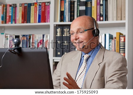 Bestager having fun while telephoning via the internet - stock photo