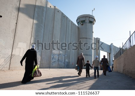 BETHLEHEM, PALESTINIAN TERRITORIES - AUGUST 17: Palestinian women pass through the Bethlehem checkpoint on the last Friday of Ramadan, West Bank, August 17, 2012. - stock photo