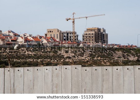 BETHLEHEM, PALESTINIAN TERRITORY - FEBRUARY 25: Construction continues in the Israeli settlement Gilo, seen over the Israeli separation wall surrounding Bethlehem, West Bank, February 25, 2013.  - stock photo
