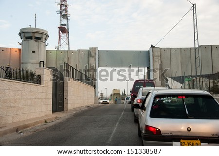 BETHLEHEM, PALESTINIAN TERRITORY - JANUARY 28: Cars wait to pass through the Israeli military checkpoint in the separation wall controlling movement between Bethlehem and Jerusalem, January 28, 2013. - stock photo