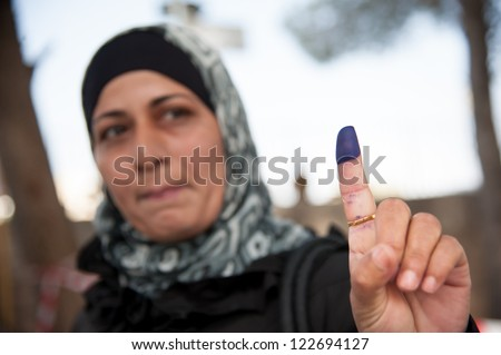BETHLEHEM, PALESTINIAN TERRITORY - OCTOBER 20: A woman shows her ink-stained finger, indicating that she has voted in Palestinian municipal elections, Bethlehem, West Bank, Oct. 20, 2012. - stock photo