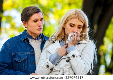 Betrayal and forgiveness couple. Girl is crying with handkerchief on outdoor. - stock photo