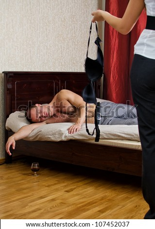 Betrayal concept: wife with a stranger bra and drunken husband in bed - stock photo