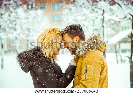 betrothed couple in love looking at each other and smiling in the snow, Horizontal color photo - stock photo