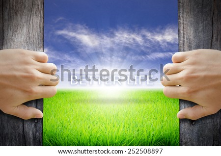 Better Life concept. Hand opening an old wooden door and found a texts floating over green field and bright blue Sky Sunrise. - stock photo