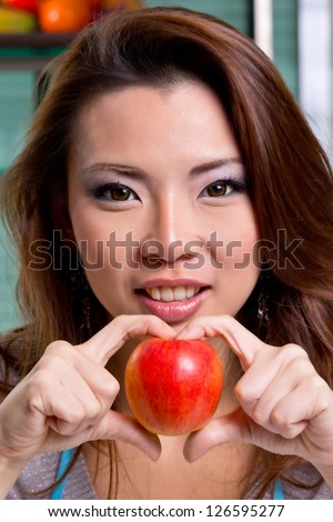 beutiful girl show apple sweet heart in kitchen (process skin tone) - stock photo