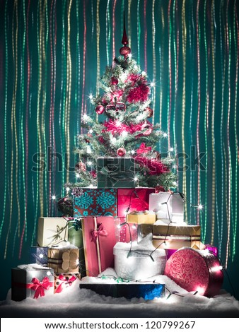 beutifuly decorated christmas tree surrounded with gift boxes covered in snow with falling colorful christmas lights in background - stock photo