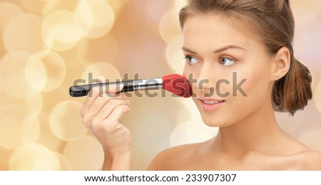 beuty, people and accessories concept - beautiful smiling woman with bare shoulders and make up brush over beige lights background - stock photo