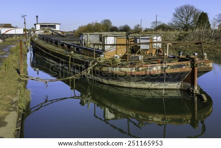 Beverley, Yorkshire, UK. A derelict river boat lays moored along the river Hull surrounded by reeds and overgrown vegetation near Beverley, Yorkshire, UK. - stock photo
