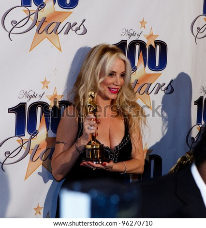 BEVERLY HILLS, CA - FEB. 26: Jennifer Young shows off father Gig Young's Oscar trophy at the 22nd Annual Night Of 100 Stars event held at The Beverly Hills Hotel on Feb. 26, 2012 in Beverly Hills, CA. - stock photo