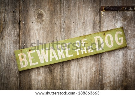 Beware Of Dog Sign on Old Worn Wood Fence - stock photo